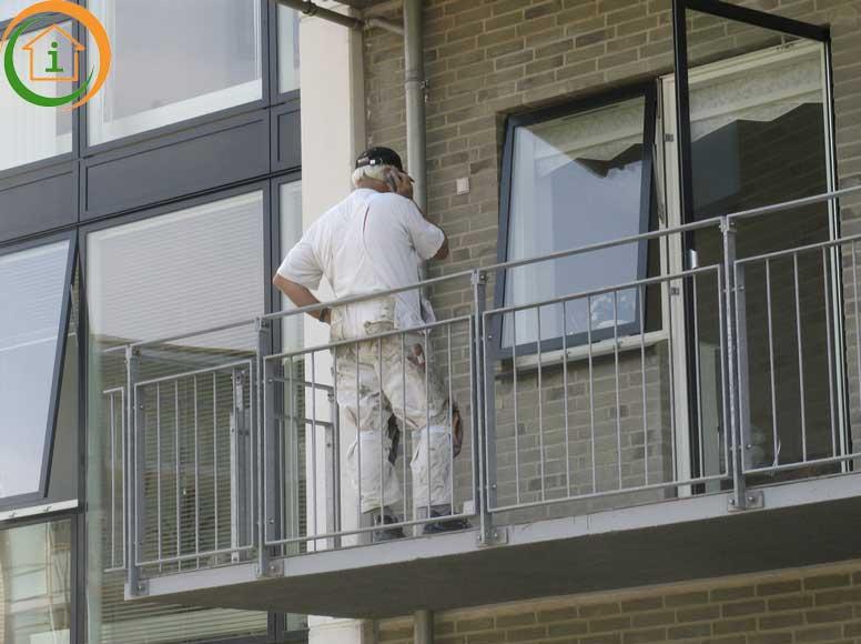 Schilder aan het werk vanaf een balkon voor de kozijnen